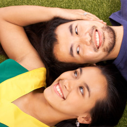 Boyfriend And Girlfriend Relaxing On The Grass In The Park